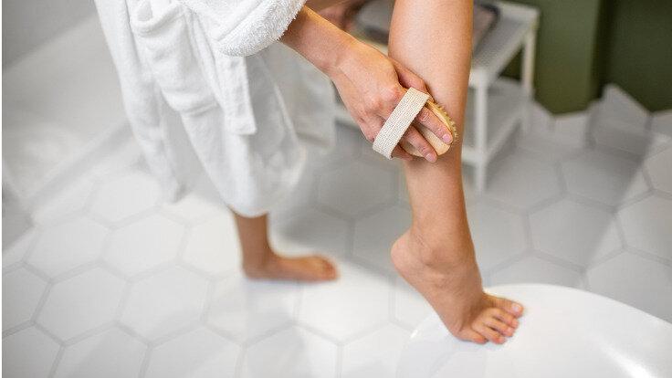 Wellness zu Hause: Frau durchblutet ihre Beine mit einer Bürstenmassage.