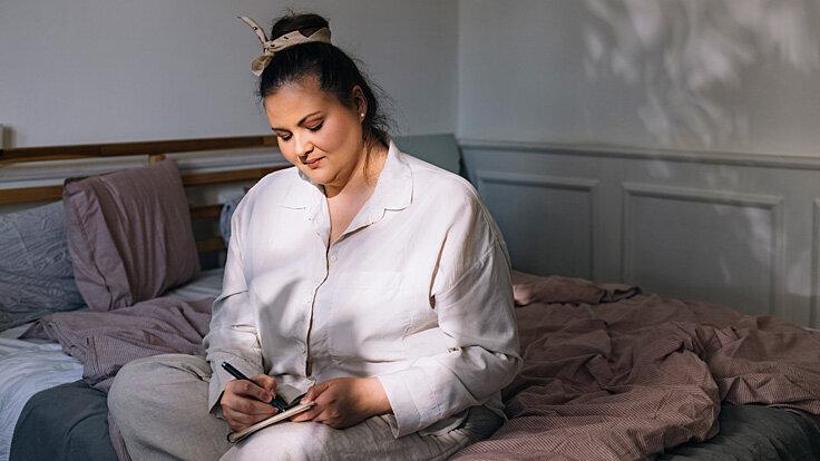 Eine Frau führt ein Schlafprotokoll, um die Ursachen ihrer Schlafstörungen herauszufinden.