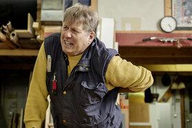 Ein Mann wird auf der Arbeit von Rückenschmerzen geplagt