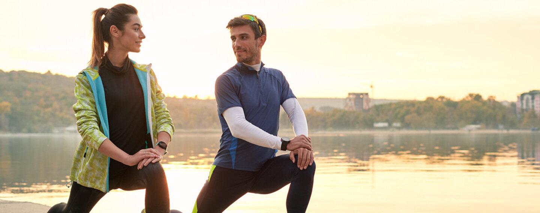 Ein Paar wärmt sich vor dem Joggen mit Dehnübungen auf und möchte so typischen Sportverletzungen vorbeugen.