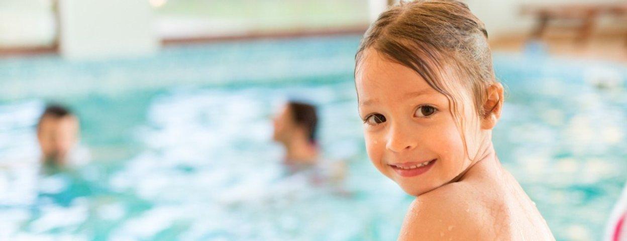 Kind sitzt im Schwimmbad am Beckenrand