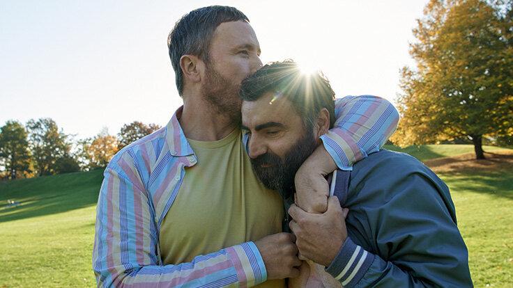 Ein Mann umarmt einen anderen Mann aus Anerkennung.