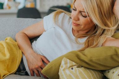Frau mit Händen auf Magen leiden von Schmerzen.
