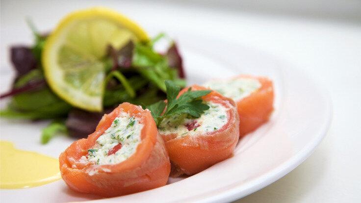 Lachsröllchen mit Frischkäse gefüllt auf einem Teller serviert sind ein toller Low-Carb-Snack.