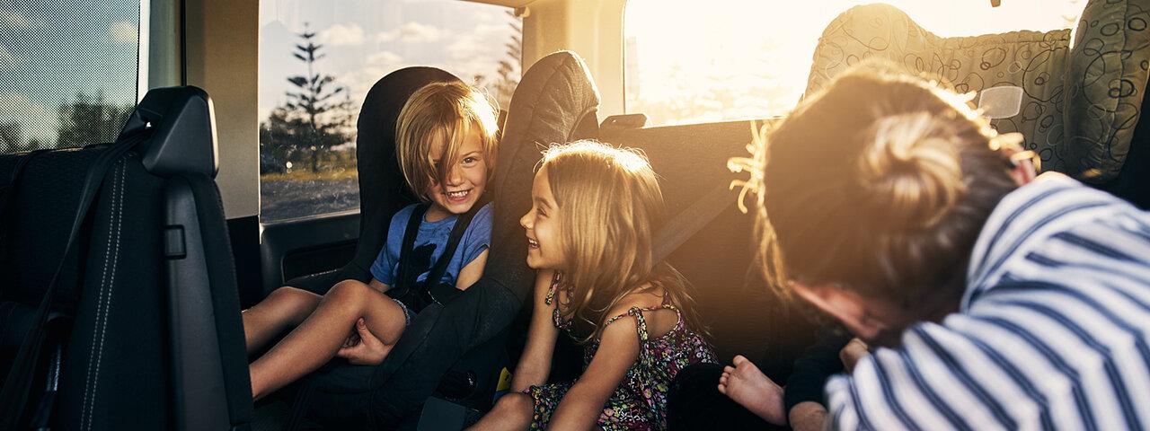 Spielende Kinder auf dem Autorücksitz