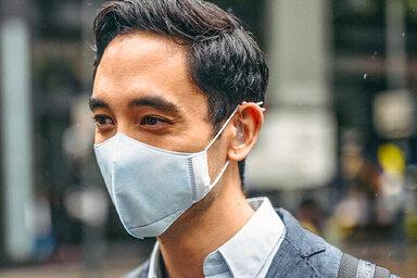 Geschäftsmann trägt Verschmutzungsmaske in der Stadt