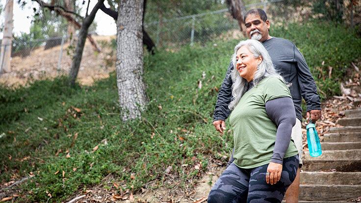 Zwei ältere Menschen gehen bewusst Treppen, um sich gesund und fit zu halten.