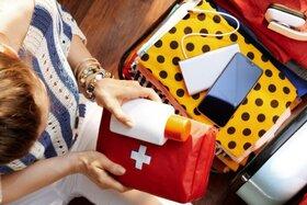 Eine Frau ist dabei, eine Reiseapotheke in den Koffer zu packen