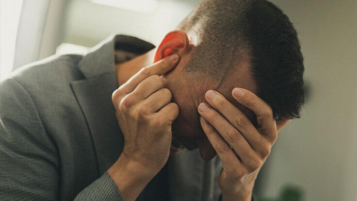 Mann leidet unter schrecklichen Clusterkopfschmerzen und hält sich den Kopf.