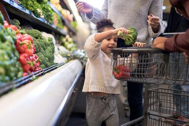 Familie geht gemeinsam einkaufen und das Kind darf mitentscheiden, was dabei im Einkaufswagen landet.