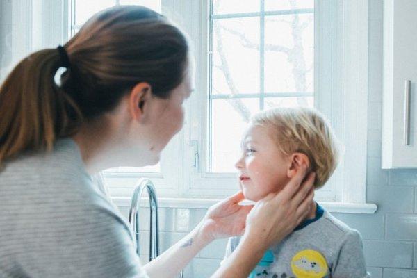 Mutter tastet Jungen mit schmerzendem Ohr am Kopf ab