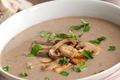Pilzsuppe mit Champignons in einer weißen Suppenschüssel serviert.