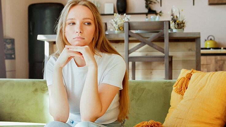 Eine Frau sitzt auf dem Sofa und schaut in die Leere – sie prokrastiniert.