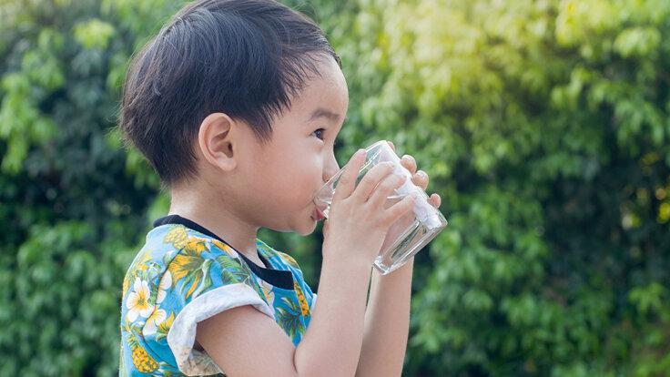 Ein Mädchen trinkt Wasser aus einem Glas, weil viel Trinken gesund ist.
