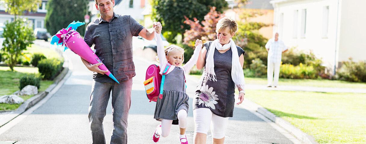 Eltern schwingen ihr Kind zwischen sich hin und her am Tag der Einschulung.