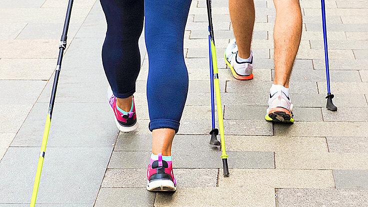 Beine von Personen beim Nordic Walking mit Trekkingstöcken.