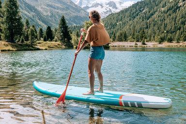 Eine junge Frau macht Stand-up-Paddling auf einem Bergsee.