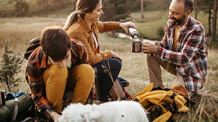 Eine Familie macht eine Pause auf ihrer Wandertour und trinkt Tee.