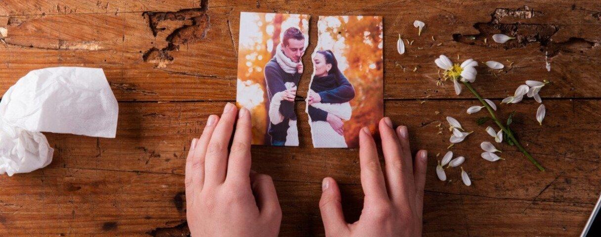 Zerissenes Pärchenfoto, dass von Frauenhänden festgehalten wird, neben benutzten Taschentüchern und einer zerrupften Blume