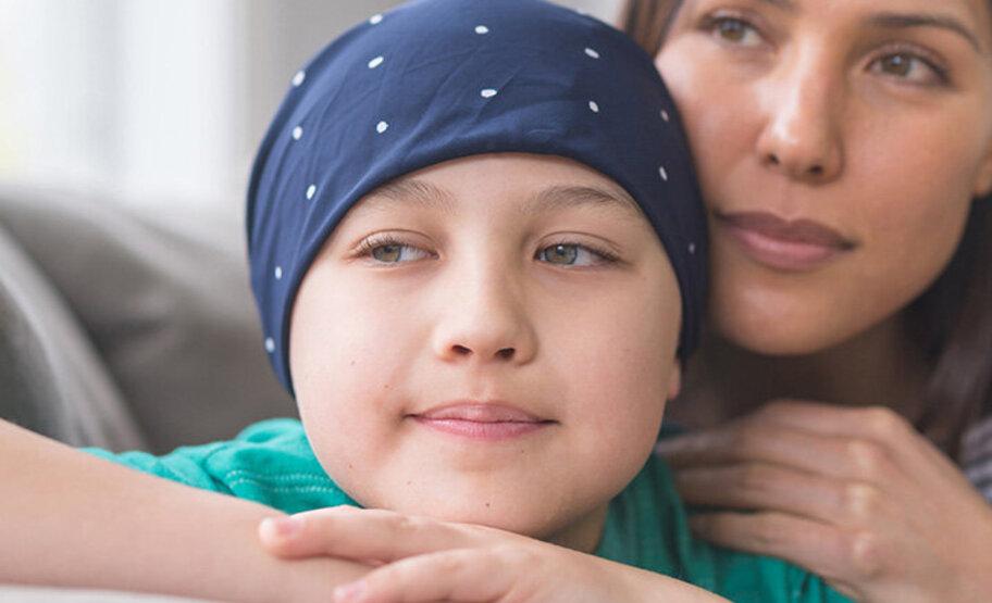 Mutter und Kind sitzen auf der Couch und schauen in die Ferne. Das Kind ist an Leukämie erkrankt.