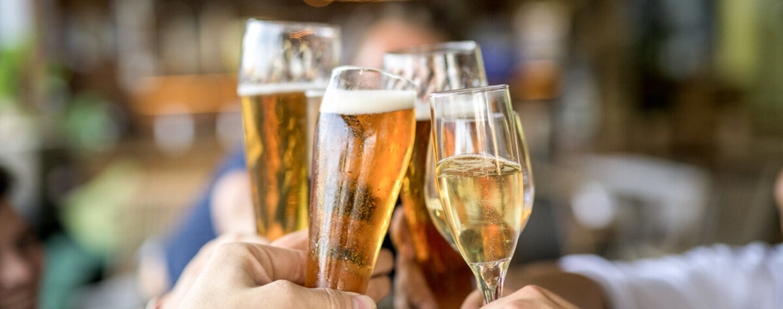 Freunde sitzen im Biergarten und stoßen mit alkoholischen Kaltgetränken an.