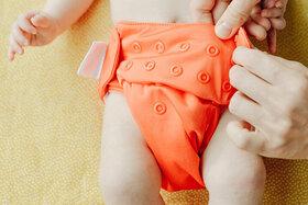 Baby wird mit einem orangefarbenem Windelhöschen gewickelt.