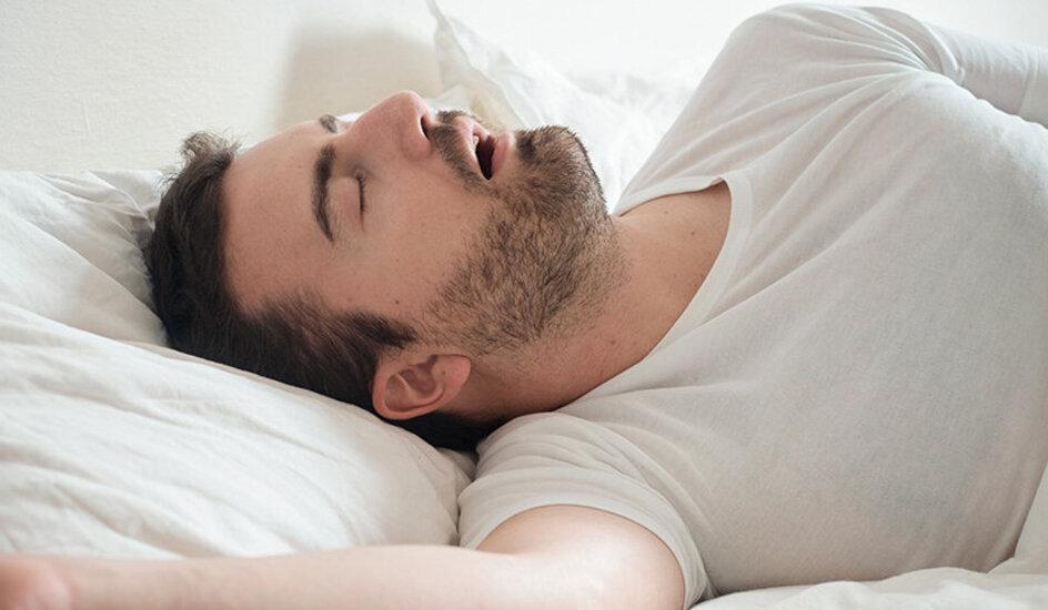 Ein Mann liegt mit offenem Mund im Bett und schnarcht
