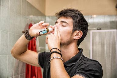 Junger Mann benutzt Nasenspray, weil er unter einer Nasenspraysucht leidet.