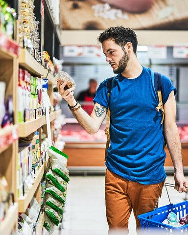 Kunde im Supermarkt checkt den Nutri-Score vom Produkt.