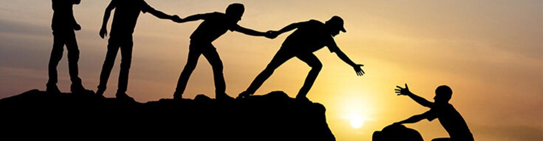 Eine Bergsteigergruppe bildet eine Kette, um jemandem bei der Überwindung eines Spalts zu helfen