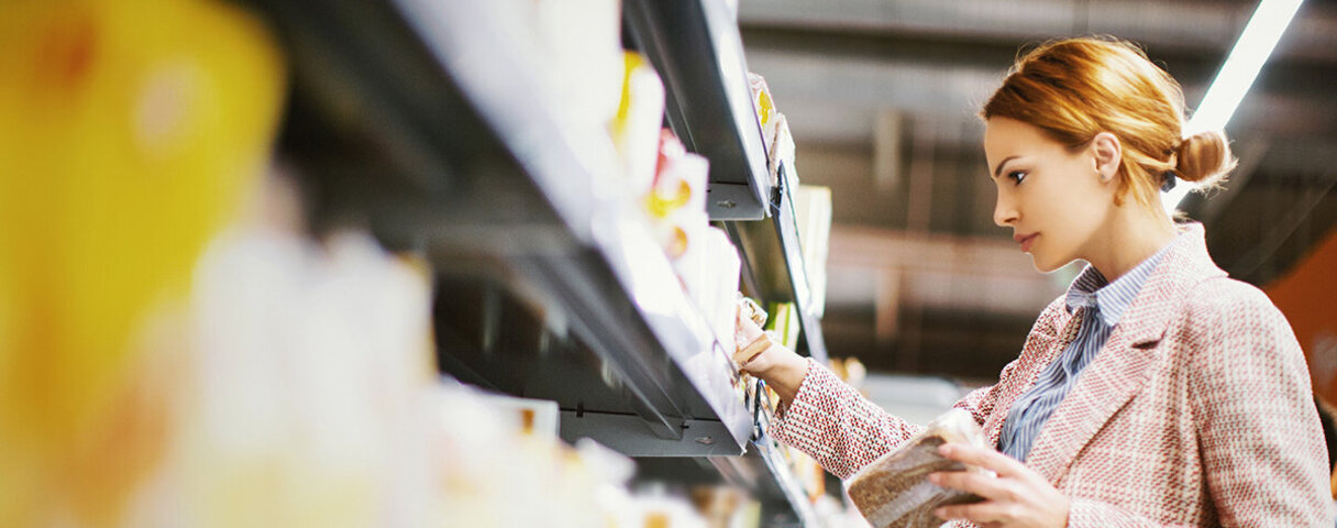 Frau mit Zöliakie schaut im Supermarkt nach glutenfreien Produkten.