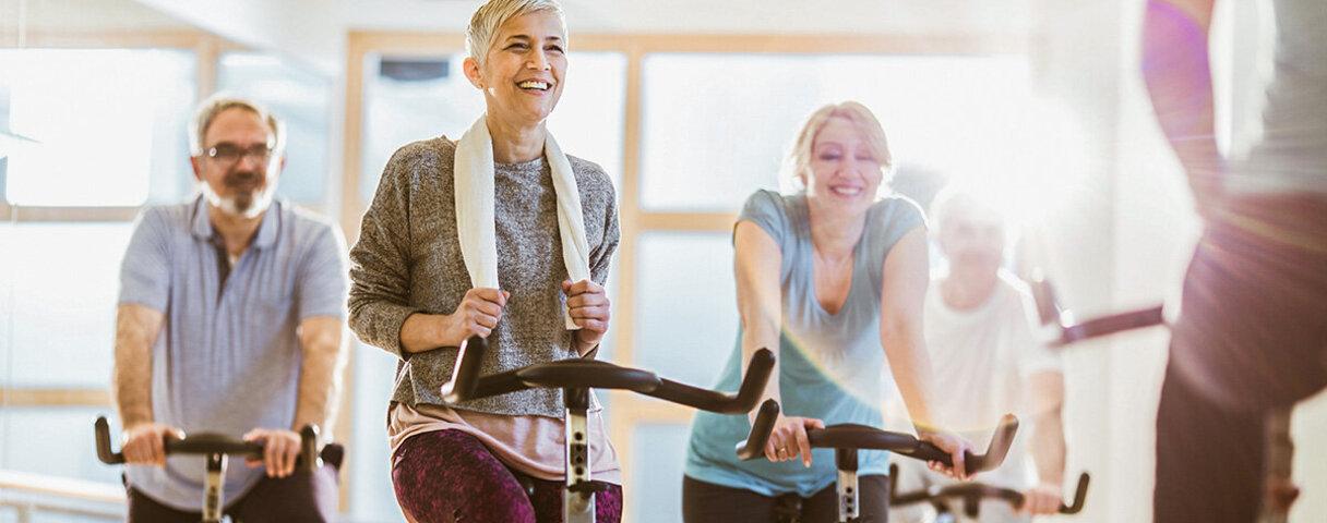Ein Gruppe sportlicher Personen machen Spinning in einem Fitnessstudio.
