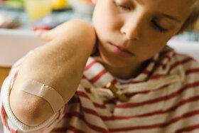Kleiner Junge hat sich am Arm verletzt und wurde mit einem Pflaster versorgt.