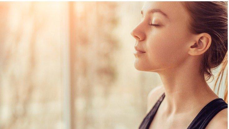 Eine Frau nimmt mit geschlossenen Augen einen tiefen Atemzug