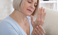 Ältere Frau massiert sich die Finger, weil sie unter Gicht leidet.