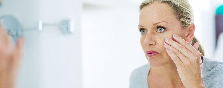 Eine Frau schaut sich ihre Augen genau im Spiegel an.