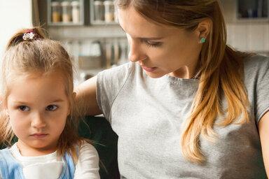 Frau legt den Arm um ein schmollendes Kind