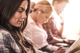 Eine Frau sitzt neben zwei Mitreisenden im Flugzeug und liest ein Buch