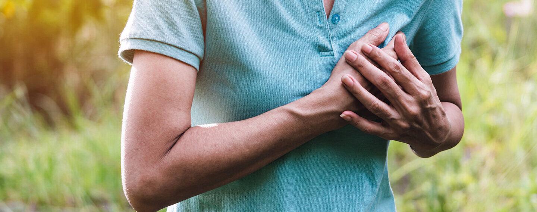 Eine Frau hält sich die Hand auf die Brust – sie hat starke Schmerzen.