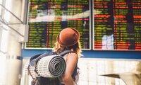 Junge Frau mit Rucksack guckt auf Anzeigentafel am Flughafen