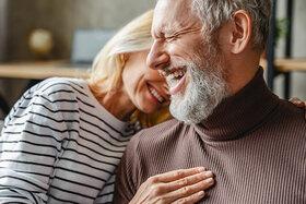 Ein älteres Paar hat das Empty Nest Syndrom überwunden und genießt die gemeinsame Zeit auf der Couch.