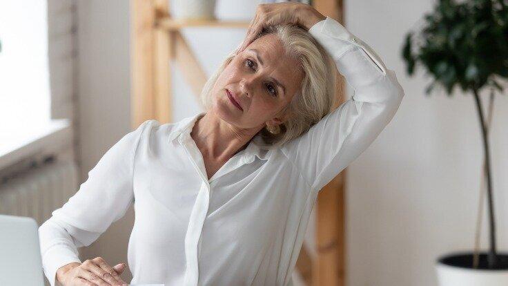 Ältere Frau streckt ihren Kopf nach rechts.