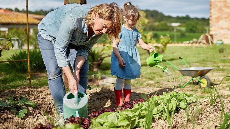 Mutter und Kind gärtnern gemeinsam an und tun etwas für die Umwelt.