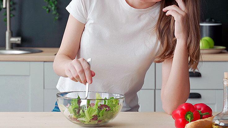 Junges, schlankes Mädchen stochert lustlos in ihrem Salat herum und mag kaum etwas essen, vielleicht ist sie von Magersucht betroffen.