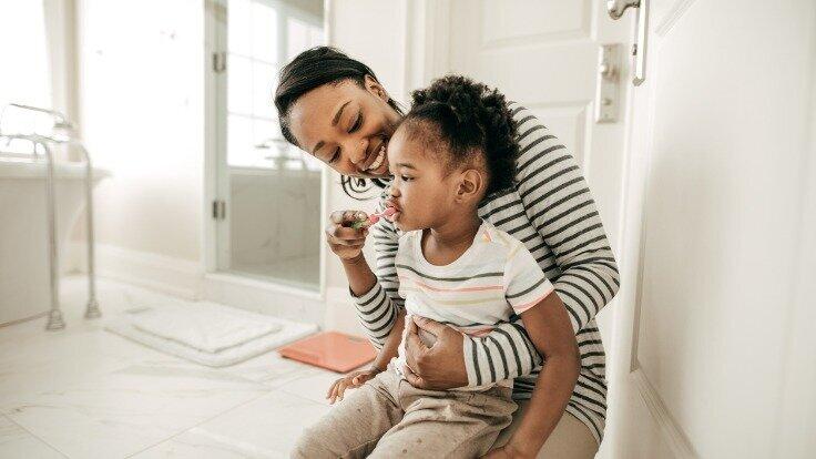 Mutter putzt mit Tochter die Zähne