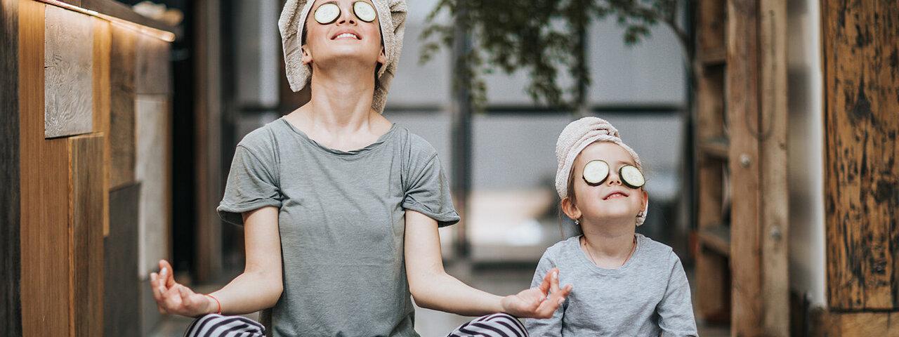 Mutter und Kind machen zusammen Entspannungsübungen.