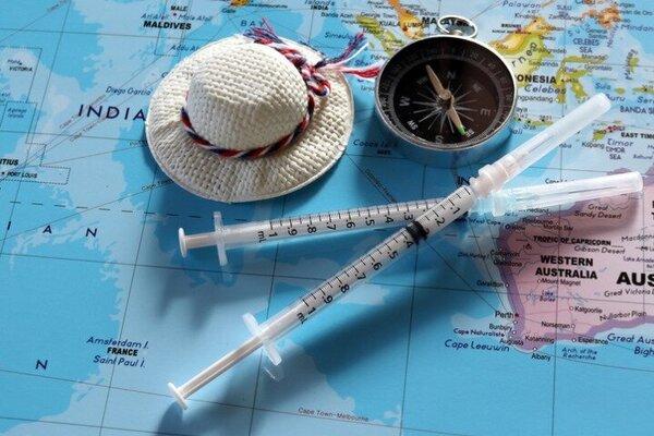 Zwei Reiseimpfungen in Spritze auf einem Atlas, in Höhe von Australien liegend, mit Mini-Reiseaccessoires