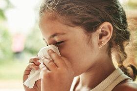Kleines Mädchen hat Heuschnupfen und putzt sich die Nase.