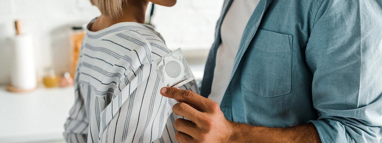Ein Paar möchte sich näherkommen. Der Mann hat ein Kondom in der Hand.
