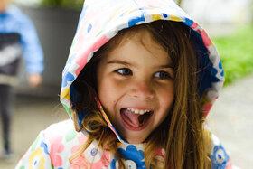 Mädchen lacht beim Spielen mit Freunden.